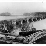 Before the Civil War the Alexandria Aqueduct connected to the C&O Canal to carry barge traffic across the Potomac River to Virginia markets. This view shows the aqueduct before the toll road with the C&O Canal in the foreground. Credit: Chesapeake & Ohio Canal National Historical Park