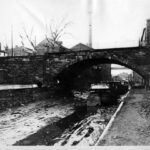 Photograph of the C & O Canal taken in the 1880s. The canal has been drained of water and boats sit in the silt waiting for the boating season. Credit: National Park Service
