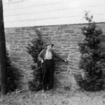 Man standing next to building