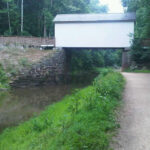 Even though it may look like a covered bridge, the wench house actually held within its wall the machinery used to place a stop gate in place during high water as well as unexpected breaks in the canal which could result in major water loss in the prism. Credit: Chesapeake & Ohio Canal National Historical Park