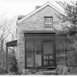 View of the enclosed porch addition to Lockhouse 10. As a part of the rehabilitation of the lockhouse in the 1930s, upgrades such as indoor plumbing, modern heat and electricity were added. Credit: National Park Service
