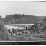 The Shawnee Canoe Club took many trips down the C & O Canal on either canoes or packet boats with their family. One of the members peers over the stone wing wall at the rushing water of the Potomac hurdling over Dam 4. Credit: Shawnee Canoe Club Collection, Chesapeake & Ohio Canal National Historical Park