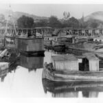Barges wait for their turn to be filled with their coal cargo. A repair scow is also seen in this photograph. Credit: Chesapeake & Ohio Canal National Historical Park