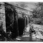 The Tonoloway Aqueduct uses a natural rock outcropping as a peir to support its arch. In the upper right corner of the photograph is a crossing canal barge. Credit: Chesapeake & Ohio Canal National Historical Park