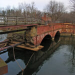 The upstream arch of the aqueduct collapsed after a flood in 1971. A bridge now carries pedestrians partway across the mouth of Seneca Creek. Note the red sandstone, quarried and cut just upstream of the lock. Credit: Doug Zveare