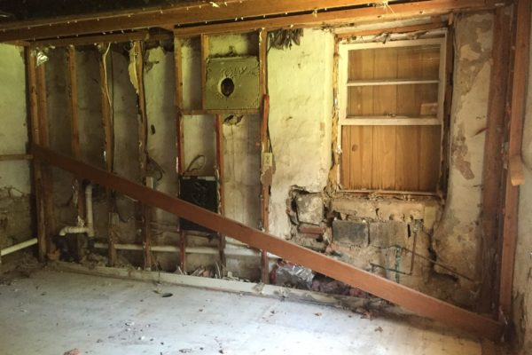 Post-demo: Downstream wall in kitchen, with water-damaged window base to right.